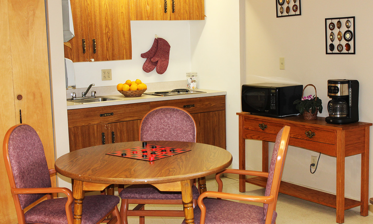 Small Group Table with Checkers In Front of Sink and Kitchen Devices